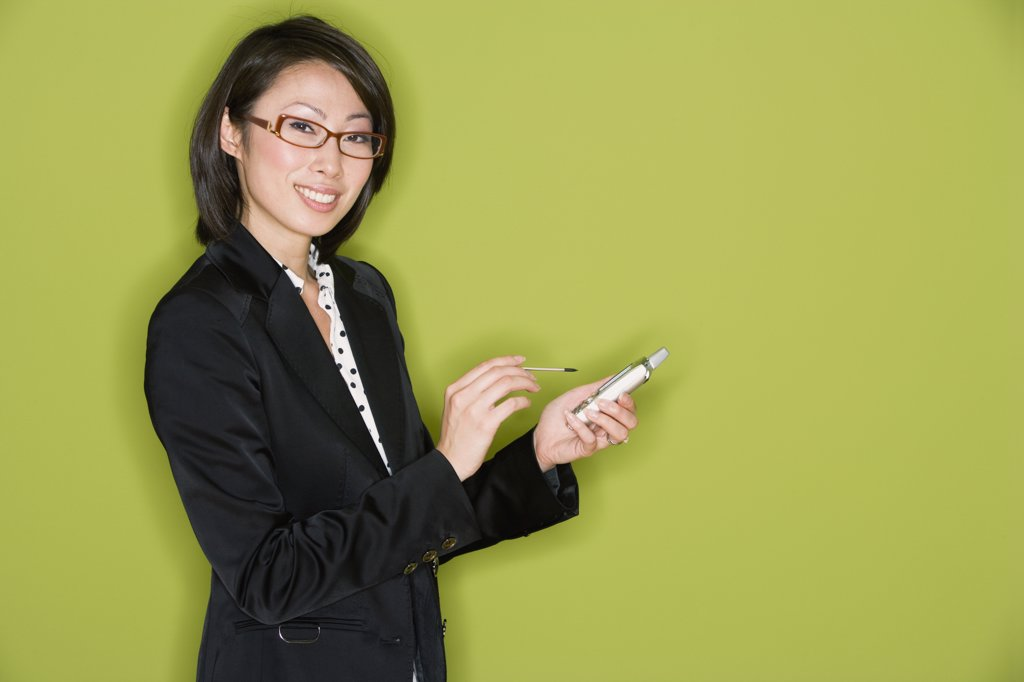 Studio shot of Asian businesswoman with electronic organizer : Stock Photo