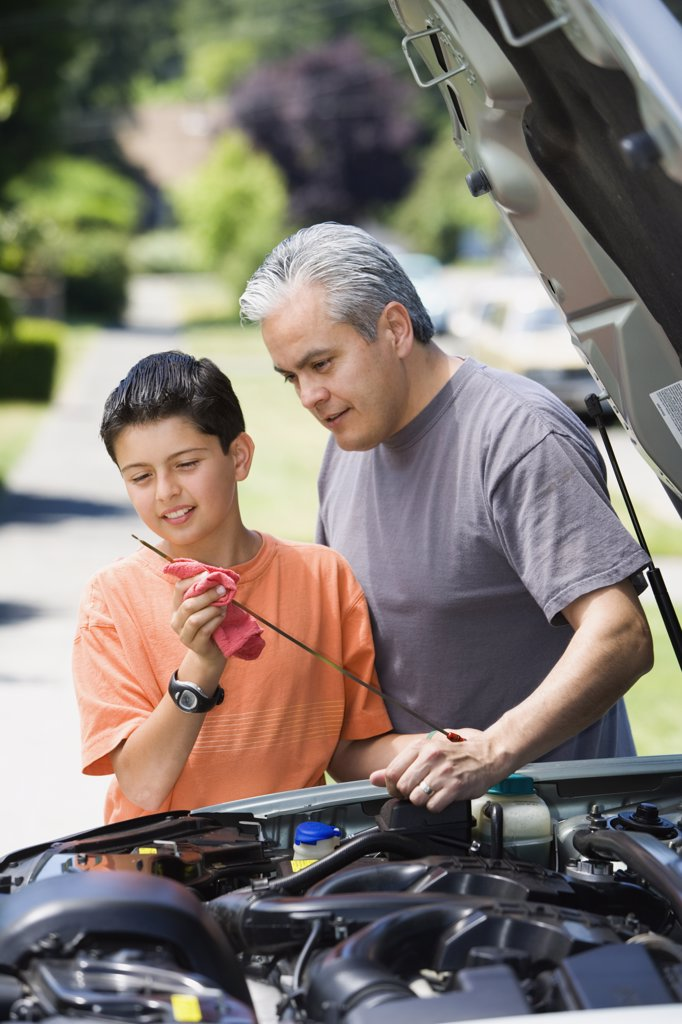 Stock Photo: 1589R-28328 Hispanic father and son checking oil in car