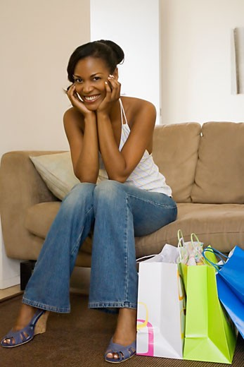 Stock Photo: 1589R-28413 African woman smiling on sofa next to shopping bags