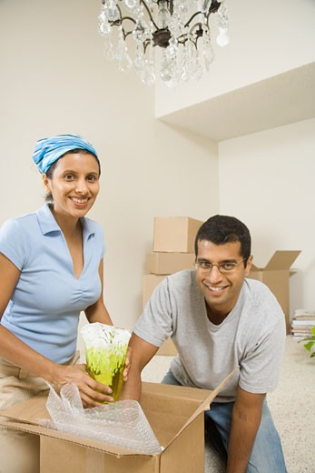 Indian couple unpacking moving boxes indoors : Stock Photo