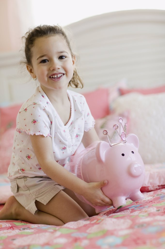 Stock Photo: 1589R-28540 Young girl with piggy bank on bed