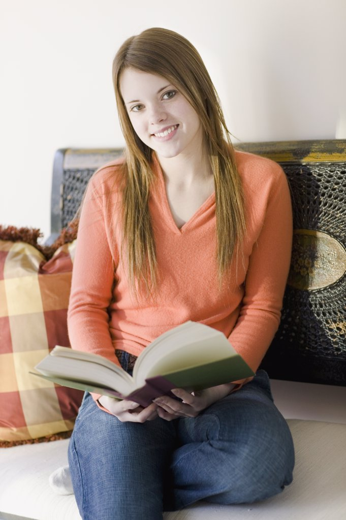 Stock Photo: 1589R-28554 Young woman sitting on floor reading