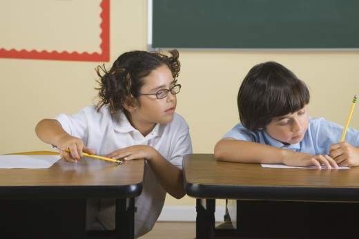 Stock Photo: 1589R-28847 Girl looking at what classmate is writing in classroom