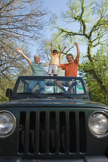 Stock Photo: 1589R-28880 Grandparents and grandson standing in jeep with arms raised