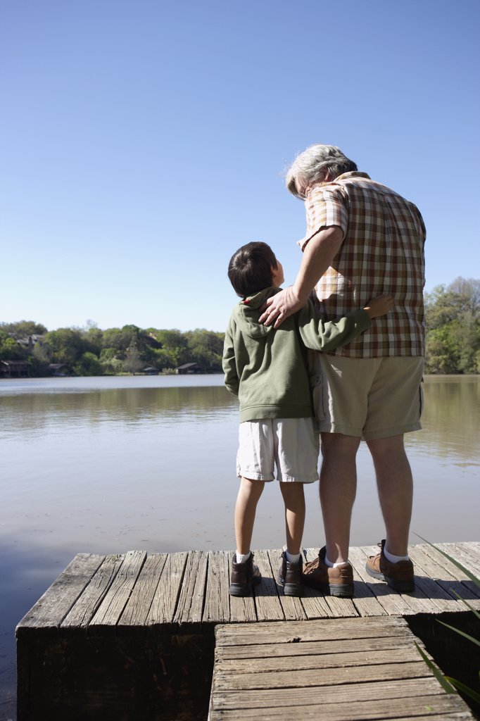 Stock Photo: 1589R-28909 Grandfather and grandson standing on wooden dock