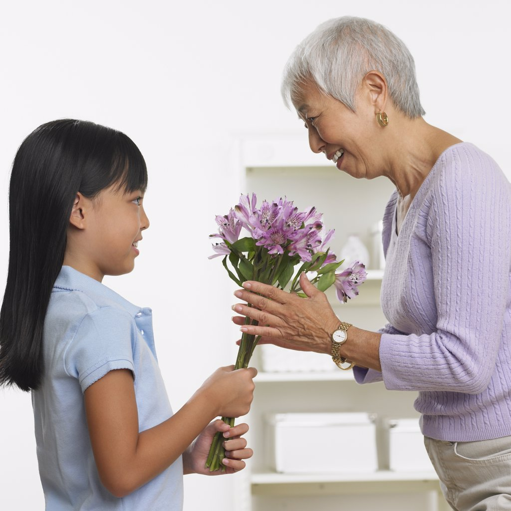 Stock Photo: 1589R-29007 Asian girl giving grandmother bouquet of flowers