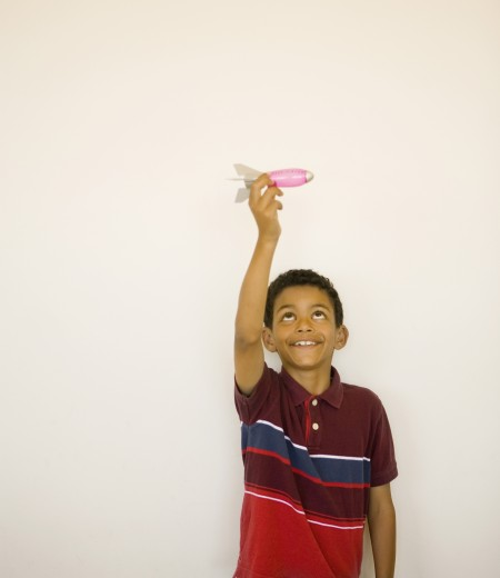 Studio shot of boy playing with toy missile : Stock Photo