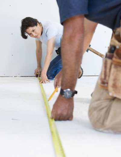 Stock Photo: 1589R-29324 Couple in tool belts measuring floor