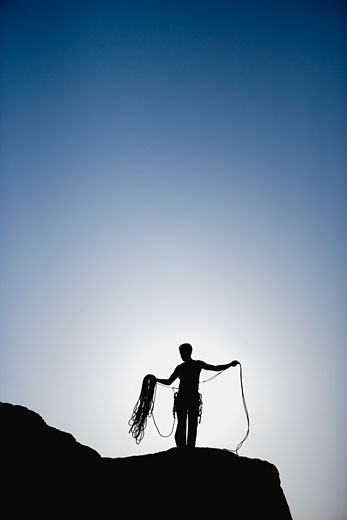 Stock Photo: 1589R-29421 Silhouette of rock climber with rope on mountain