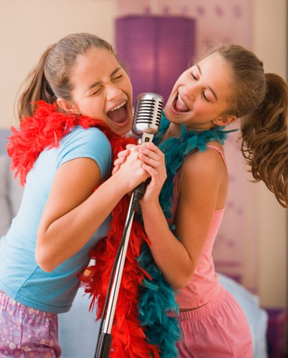 Stock Photo: 1589R-29503 Hispanic sisters singing into microphone in bedroom