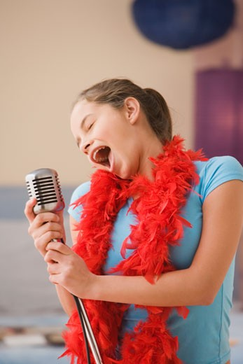 Stock Photo: 1589R-29504 Hispanic girl singing into microphone in bedroom