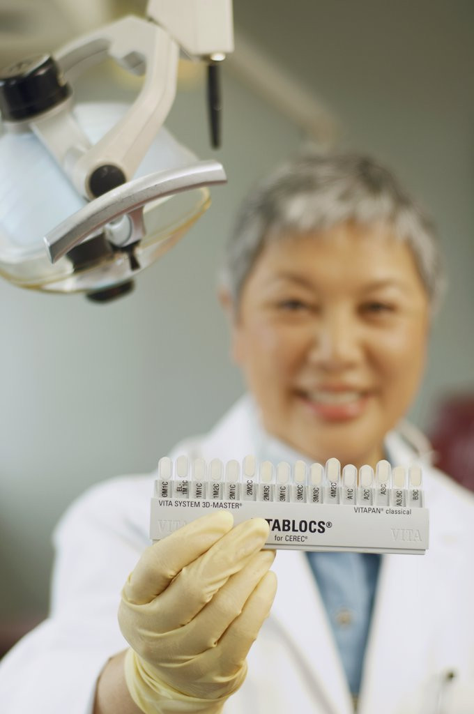 Senior Asian female dentist holding tooth color samples : Stock Photo