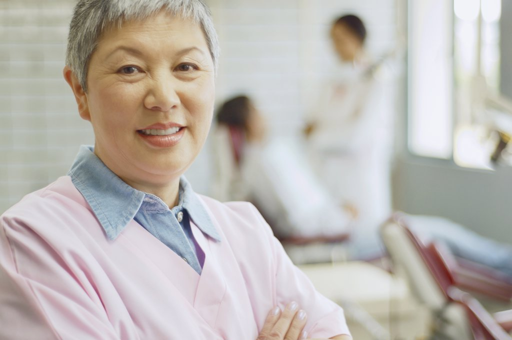 Stock Photo: 1589R-29817 Senior Asian female dental assistant with dentist and patient in background
