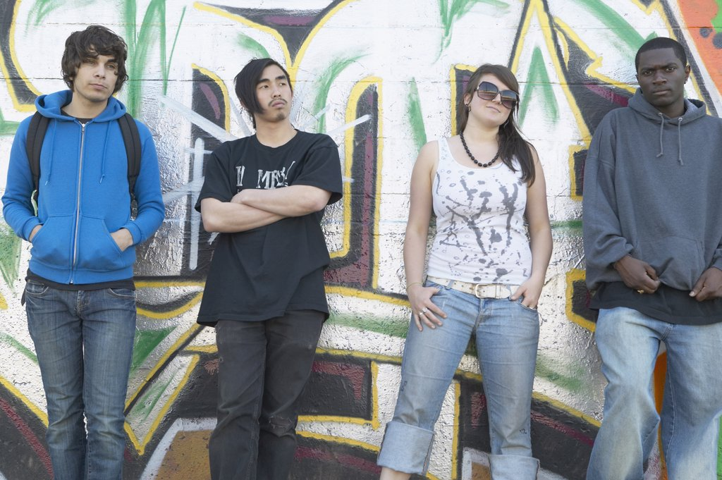 Group of young adults leaning against graffitied wall : Stock Photo