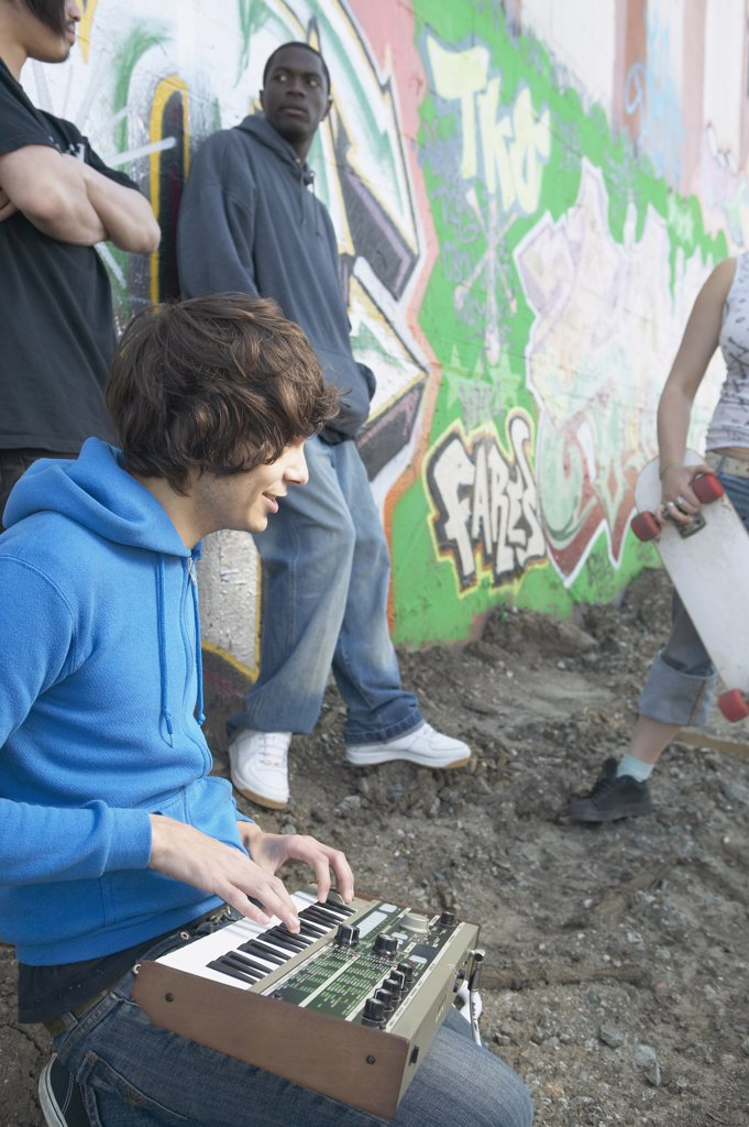 Young man with music equipment and friends next to graffitied wall : Stock Photo