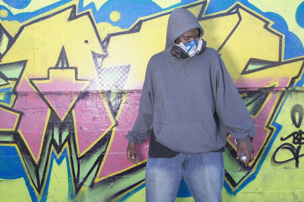 African man with spray paint next to graffitied wall : Stock Photo
