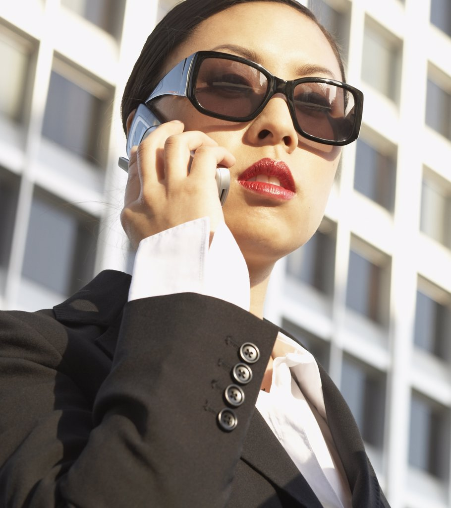 Stock Photo: 1589R-29897 Low angle view of Asian businesswoman using cell phone