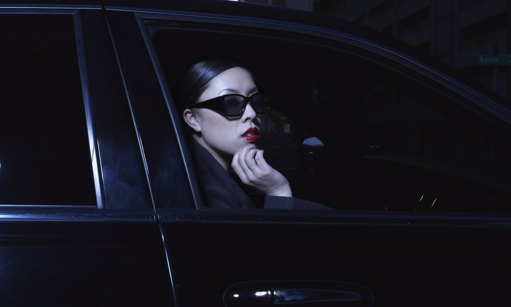 Asian woman sitting in car wearing sunglasses : Stock Photo