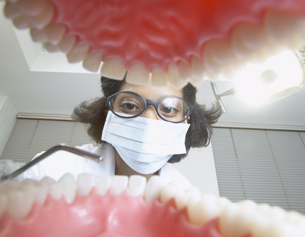 Shot from mouth looking out at African female dentist : Stock Photo
