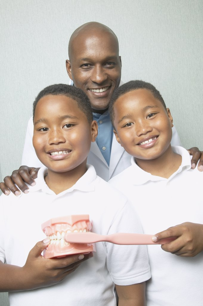 African male dentist with twin boys holding toothbrush and model of teeth : Stock Photo