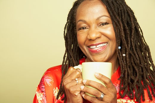 Studio shot of middle-aged African woman smiling with coffee : Stock Photo