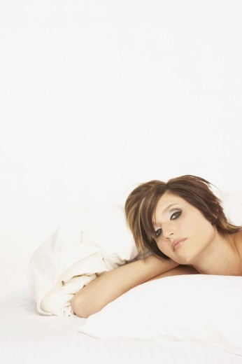 Stock Photo: 1589R-30438 Woman laying on bed with arm behind head