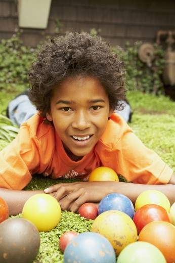 Stock Photo: 1589R-30518 African boy laying in grass with balls
