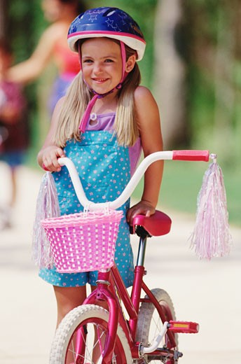 Young girl holding bicycle with tassels and basket : Stock Photo