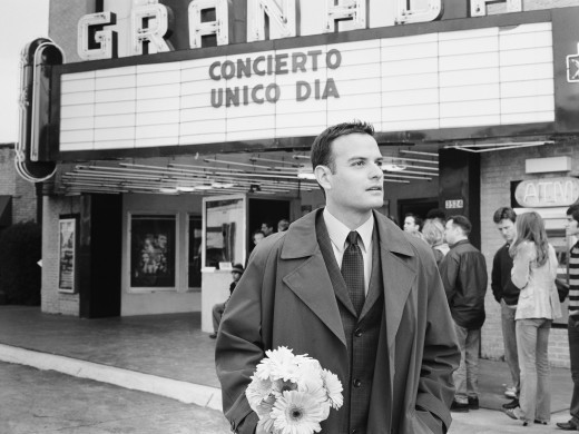 Man in suit with flowers waiting in front of movie theater : Stock Photo