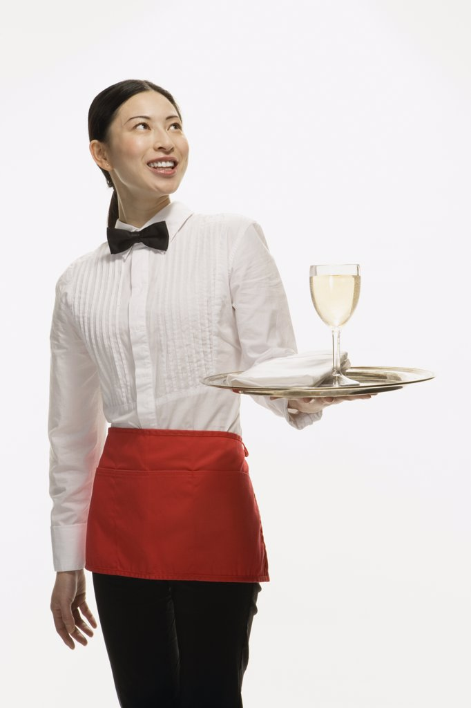 Studio shot of Asian waitress holding tray with wine glass : Stock Photo