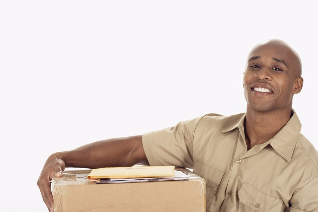 Stock Photo: 1589R-30888 Studio shot of African delivery man with package