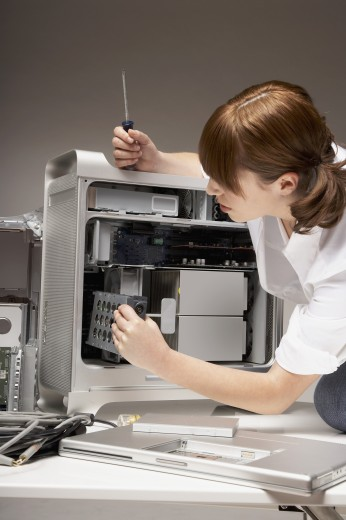 Woman installing hardware into computer : Stock Photo