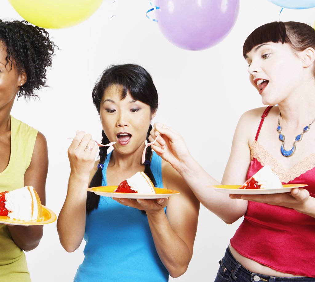 Stock Photo: 1589R-31054 Studio shot of three women eating cake with balloons