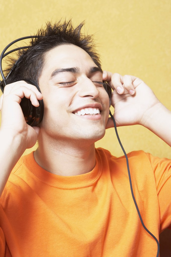Close up of young man listening to headphones indoors : Stock Photo