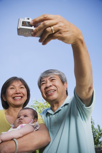 Asian grandparents holding baby grandchild and taking photograph : Stock Photo