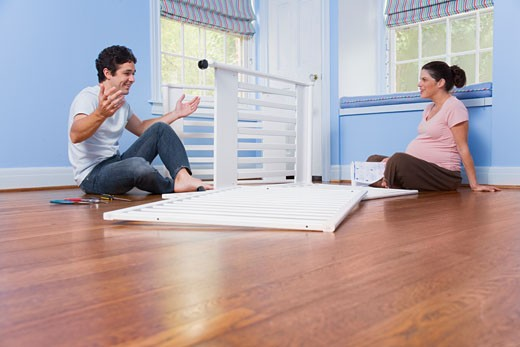 Pregnant couple putting crib together : Stock Photo