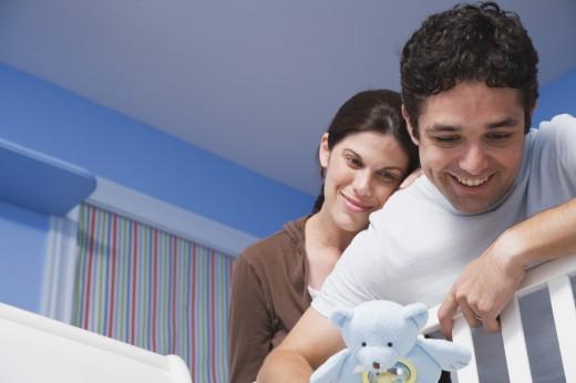 Hispanic couple leaning over crib railing with toy : Stock Photo