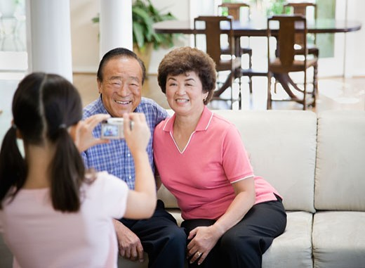 Stock Photo: 1589R-31491 Asian girl taking photograph of grandparents