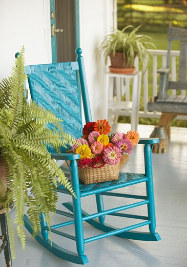 Stock Photo: 1589R-31743 Basket of flowers and rocking chair on porch
