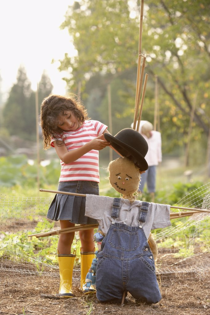 Stock Photo: 1589R-31762 Young Hispanic girl putting hat on scarecrow