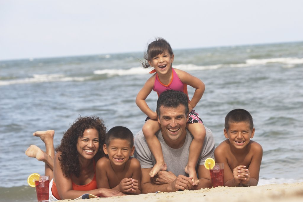Stock Photo: 1589R-31786 Hispanic family laying on beach
