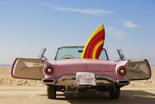 Convertible car with Just Married sign and surfboard : Stock Photo