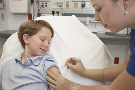 Young boy receiving injection from nurse : Stock Photo
