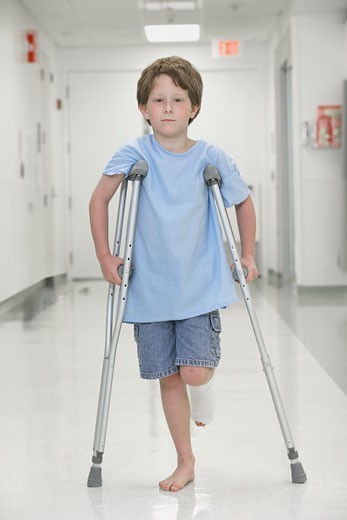 Stock Photo: 1589R-32367 Young boy with broken leg walking on crutches