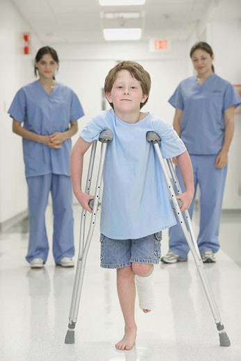 Stock Photo: 1589R-32368 Nurses watching boy with broken leg walk with crutches