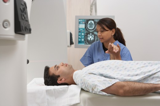Stock Photo: 1589R-32383 Indian nurse holding patient's hand in MRI scanner