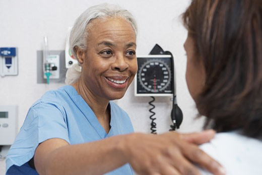 Senior African nurse reassuring female patient : Stock Photo