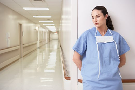 Female doctor leaning against wall in hospital corridor : Stock Photo
