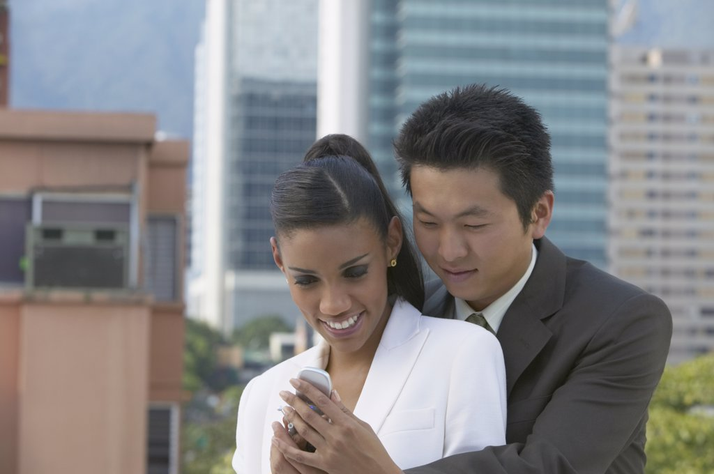 Stock Photo: 1589R-32968 Young couple looking at cell phone