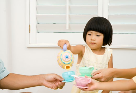 Stock Photo: 1589R-33107 Asian girl and family playing with toy tea set